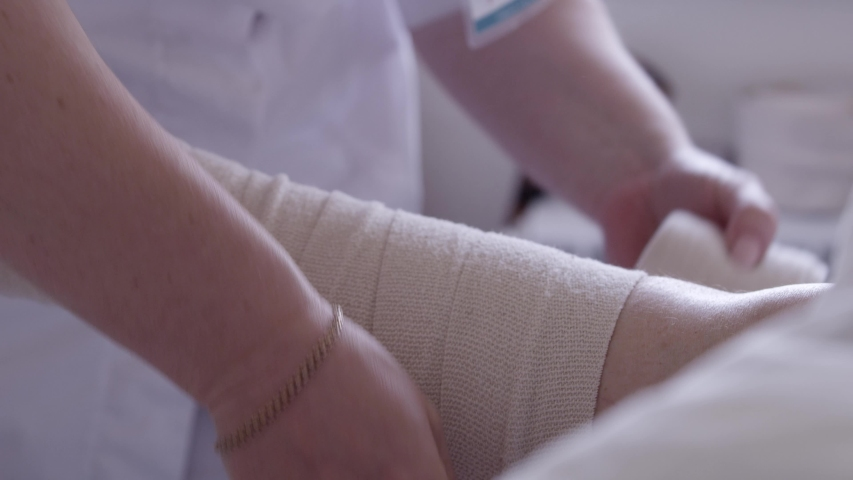 Nurse bandages a patient's leg with an elastic bandage in a hospital bed