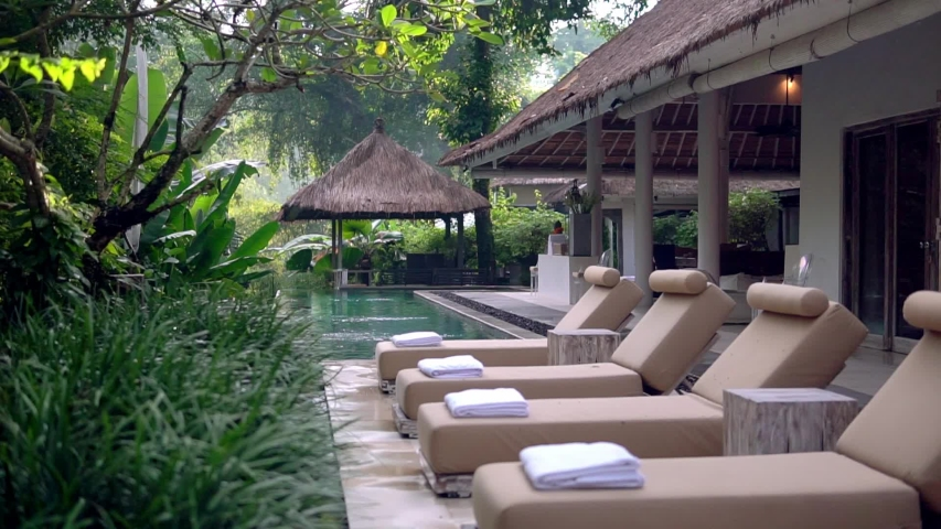 Row of lounging chairs on pool terraces in exotic hotel. Outside area with pool Royalty-Free Stock Footage #1029519158