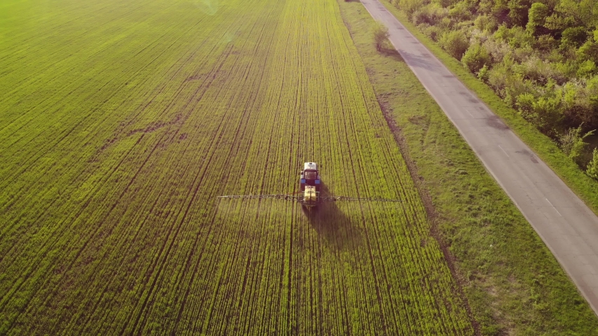 Aerial view of farming tractor spraying on field with sprayer, herbicides and pesticides at sunset. Farm machinery spraying insecticide to the green field, agricultural natural seasonal spring works. | Shutterstock HD Video #1029535574