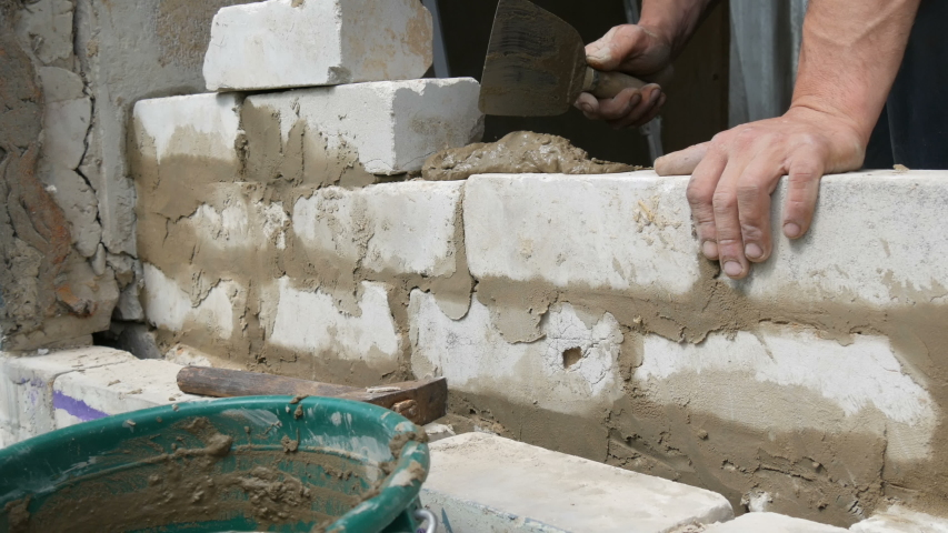 Male builder laying white brick on cement and standing wall. Hands of a man laying building bricks close up view   Shutterstock HD Video #1029554039