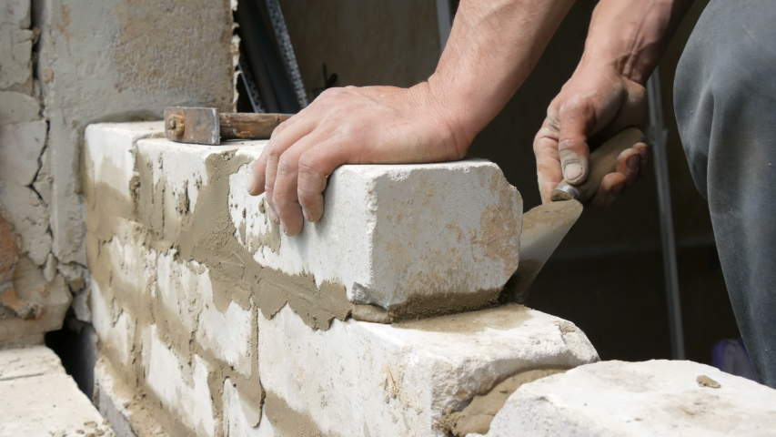 Male builder laying white brick on cement and standing wall. Hands of a man laying building bricks close up view   Shutterstock HD Video #1029554069