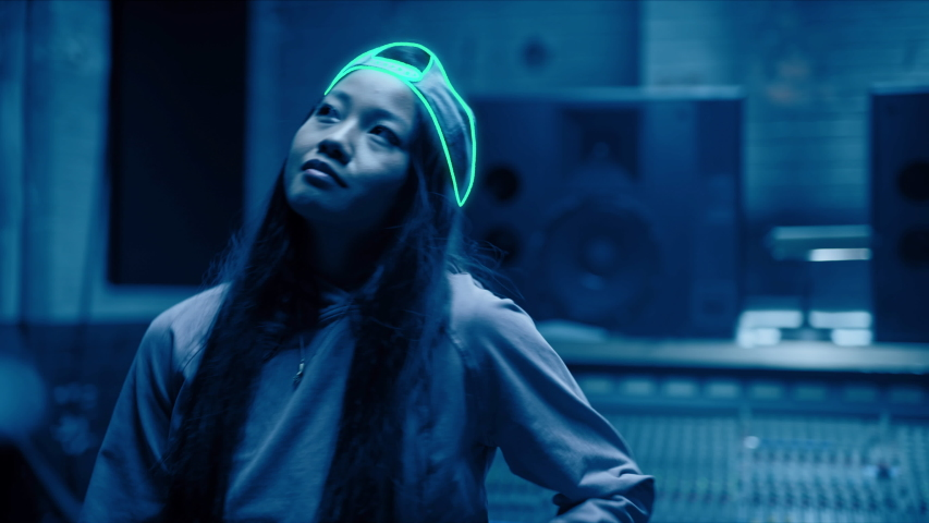R&B dancer grooving and dancing in her music studio in dark blue light. Hand drawn animation over live action footage in a grunge neon style. Shot on 4k RED camera.