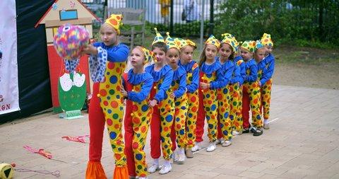LOS ANGELES, CALIFORNIA, USA - APRIL 21, 2019: Young russian girls in clown circus dress perform dancing at cultural festival, 4K