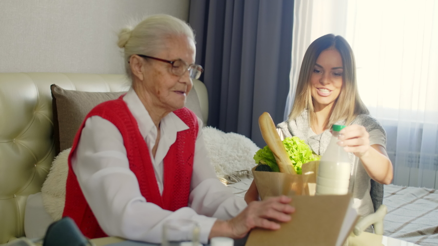 Senior woman in glasses sitting at table in bedroom and reading a book while young cheerful female volunteer bringing paper bag with groceries, speaking and taking off milk and bread