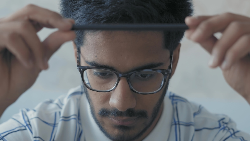 Close-up, Indian Student in Glasses Rotates in Pencil Hands and Pensively Looks Before Himself, Prepares for Exams | Shutterstock HD Video #1029600965