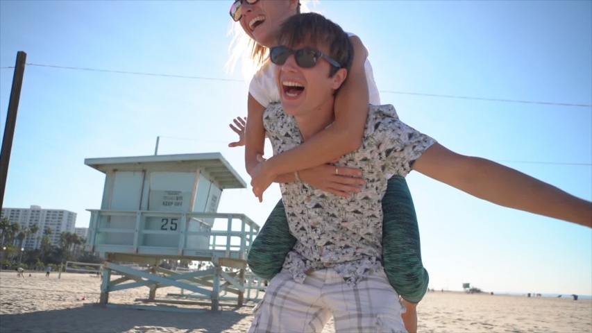Piggy back at the beach. Young couple having fun at Santa Monica beach Los Angeles. Slow motion