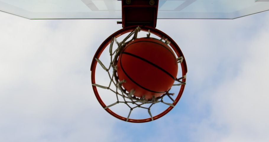 Upward view of basketball going through basketball hoop in basketball court. Sky and cloud in the background 4k