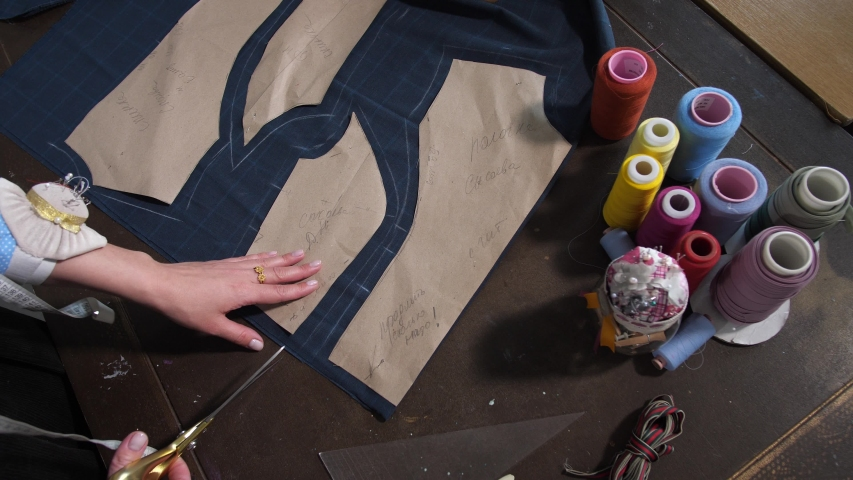 Top view of seamstress's hands carefully cutting out details of future dress from fabric lying on worktable in design workshop studio. Female clothes designer working with patterns on cloth in atelier