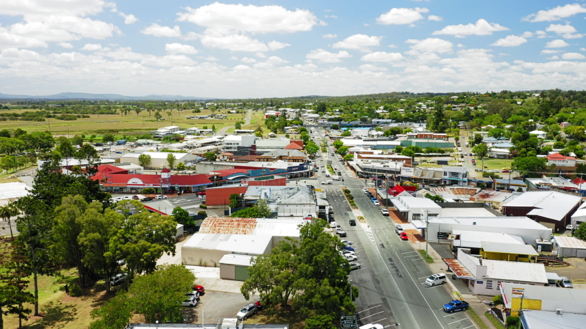 Aerial shot of the town of Beaudesert in the scenic rim region of Queensland Australia. Drone rises and orbits to reveal whole town centre during midday in Summer.