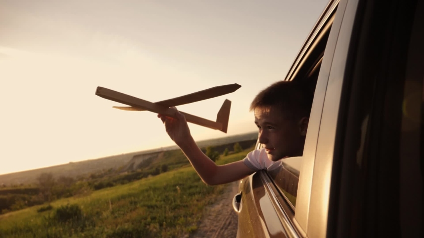 A boy with an airplane model in his hands plays traveling by car. Fantasy baby in the sun at sunset. Striving for victory and success. The concept of lifestyle and the path to success. #1029651020
