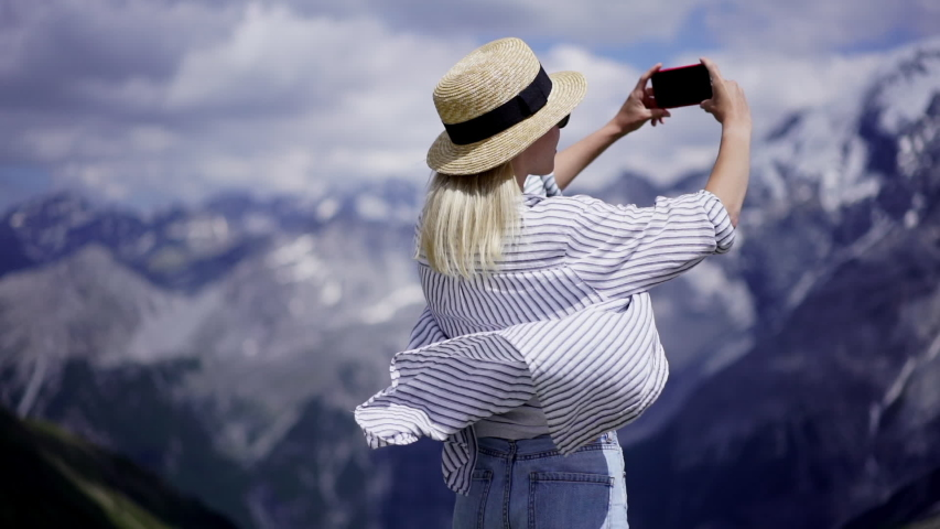Young hipster girl in casual wear holding cellular phone in hands making photo of journey in mountains, female travel blogger taking picture of breathtaking nature landscape in vacations, slow motion | Shutterstock HD Video #1029651242