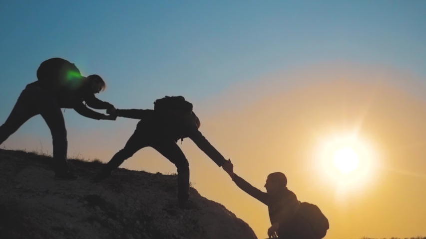 Teamwork help business travel silhouette concept. group lifestyle of tourists lends a helping hand climb the cliffs mountains. people climbers climb to the top overcoming hardships the path to victory | Shutterstock HD Video #1029668909