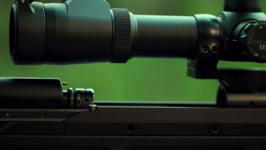 Spectacular shot of a sniper rifle. Hitting the target. The shooter will send the cartridge to the chamber. Shot at the target. Sniper performs a special operation. Slow Motion. 4K. UHD.