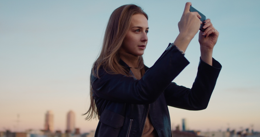 Young beautiful tourist girl with her smartphone taking a picture on the rooftop terrace with sunset views of an old town. Slow Motion. Shot on RED digital cinema camera | Shutterstock HD Video #1029670682
