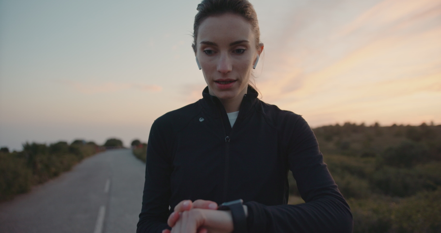 Cute woman checking tracker results an making new goal for running outdoors. Slow motion. Jogging during epic sunset. Shot on digital cinema camera, Cinematic Shot | Shutterstock HD Video #1029670715
