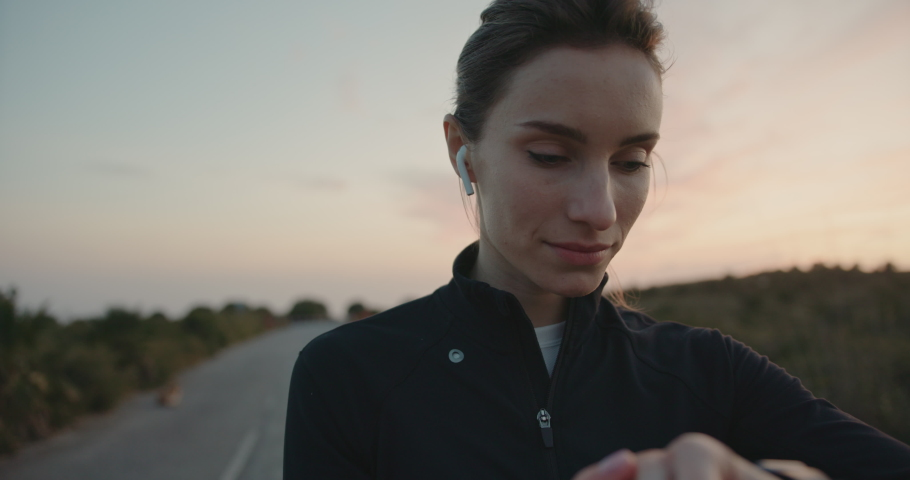 Cute woman checking results on her tracker an making new goal for running outdoors. Jogging during epic sunset. Shot on digital cinema camera | Shutterstock HD Video #1029670742