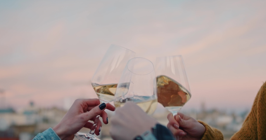 Hands cheering with glasses of white wine during the golden hour. With an old evening cityscape on their background. Slow Motion. Shot on RED digital cinema camera   Shutterstock HD Video #1029670811
