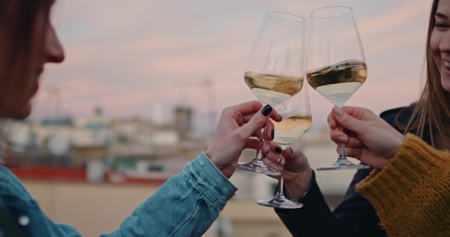 Young girls cheering and laughing with glasses of white wine during the golden hour. With an old evening cityscape of Barcelona on their Background. Slow Motion. Shot on RED digital cinema camera | Shutterstock HD Video #1029670829