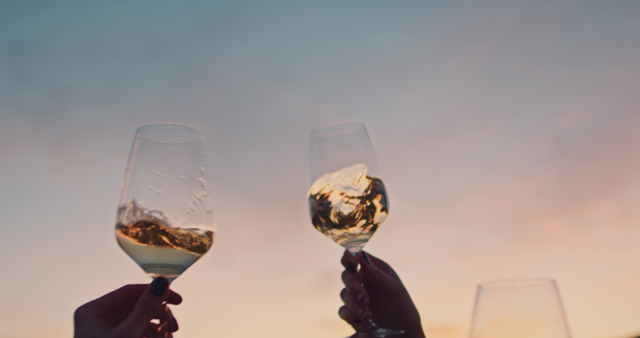 Hands of happy friends cheering celebrating holidays with wine during the epic sunset. Slow Motion. Shot on RED digital cinema camera | Shutterstock HD Video #1029670868