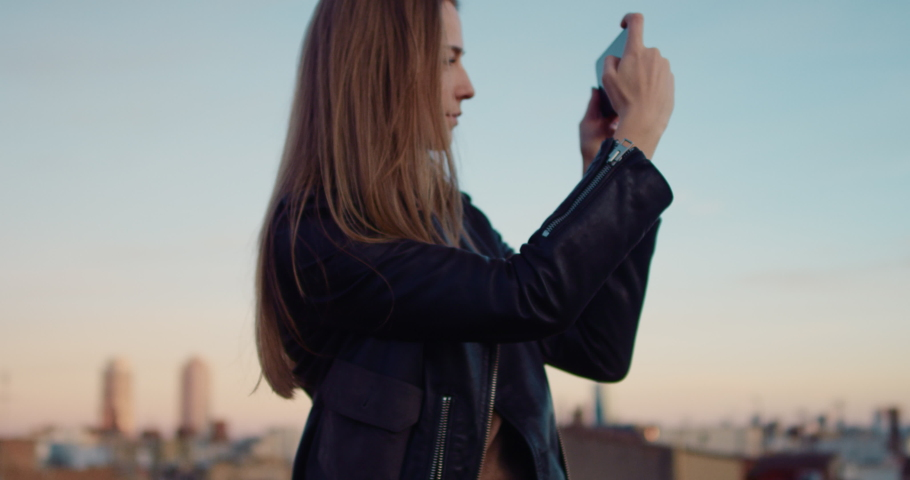 Young tourist girl taking a picture with her smartphone on the rooftop terrace with sunset views of an old town. Slow Motion. Shot on RED digital cinema camera | Shutterstock HD Video #1029670871