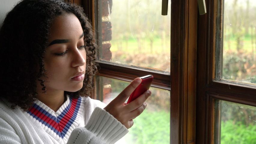 Sad beautiful mixed race African American girl teenager young woman wearing a white jumper, sitting by a window using her mobile cell phone or smartphone for social media, communications or texting Royalty-Free Stock Footage #1029677837