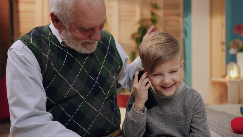 Grandpa and little smiling Caucasian boy sitting on bed. Kid holding smartphone in hand, calling. Old man looking after beloved grandson. Indoors, home. Royalty-Free Stock Footage #1029681428