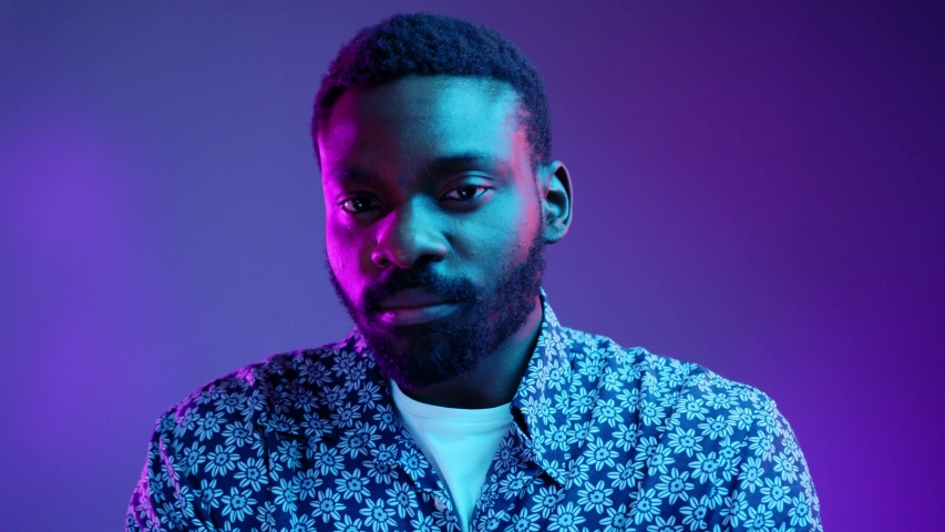 Portrait of handsome young African American male dressed in flowered shirt looking at camera with serious and confident expression on his face in neon lights. People and lifestyle concept. Male studio #1029682178