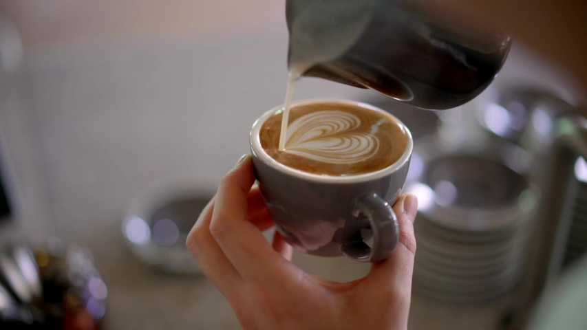 Barista pouring milk in coffee doing latte art | Shutterstock HD Video #1029697007