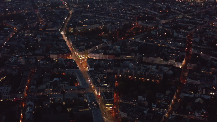 AERIAL: Birdsview over Berlin, Germany neighborhood at night with glowing street traffic city lights 4K