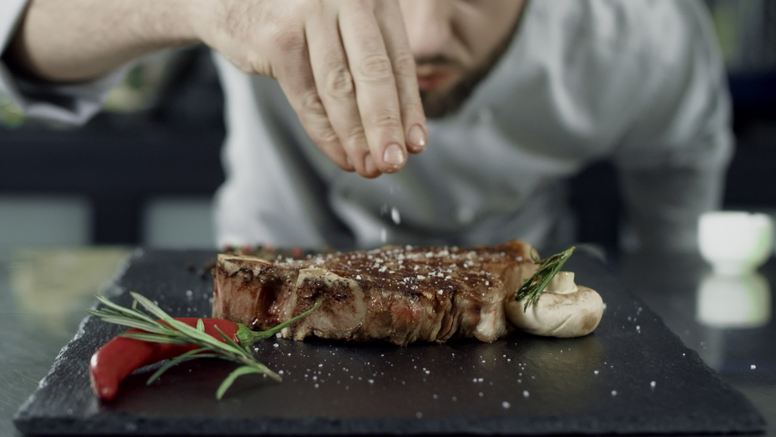 Chef salt grilled meat at stone cutting board. Closeup man hands salting steak in slow motion. Close up hands finishing ready steak. Closeup grill meat dish with vegetables at professional kitchen. Royalty-Free Stock Footage #1029702131