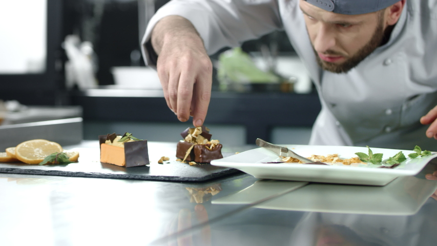 Chef decorating cake at kitchen. Closeup male chef making dessert in slow motion. Professional cook decorating cake at workplace. Young man cooking chocolate cake | Shutterstock HD Video #1029702146