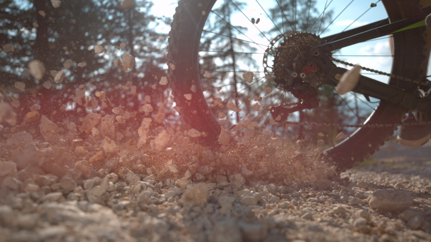 SLOW MOTION, SUN FLARE, CLOSE UP, LOW ANGLE: Cinematic shot of rocks flying as cyclist rides along a gravel path. Unrecognizable extreme bike rider brakes while mountain biking sending rocks flying.
