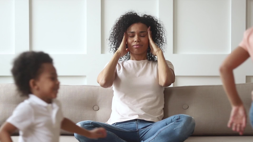 Stressed upset african american mom feeling migraine headache tired of too active kids running around, annoyed single black mother desperate about two difficult naughty children misbehaving at home  #1029713954