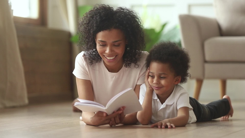 Loving african american mother telling fairy tale story to smart cute kid son laying on warm floor together, caring mixed race mom babysitter holding reading book to little child boy learning at home Royalty-Free Stock Footage #1029713969