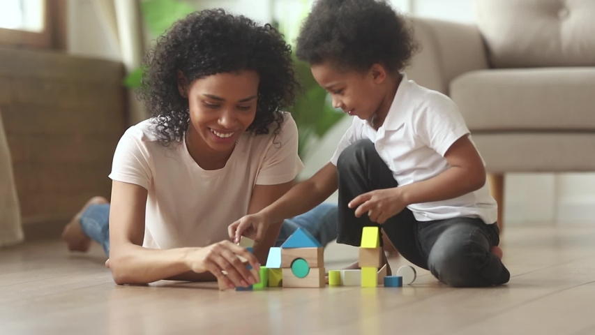 Happy loving african mom babysitter playing with cute small kid son laying on warm floor, caring mixed race mother nanny helping little child boy building constructor castle of wooden blocks at home Royalty-Free Stock Footage #1029713972