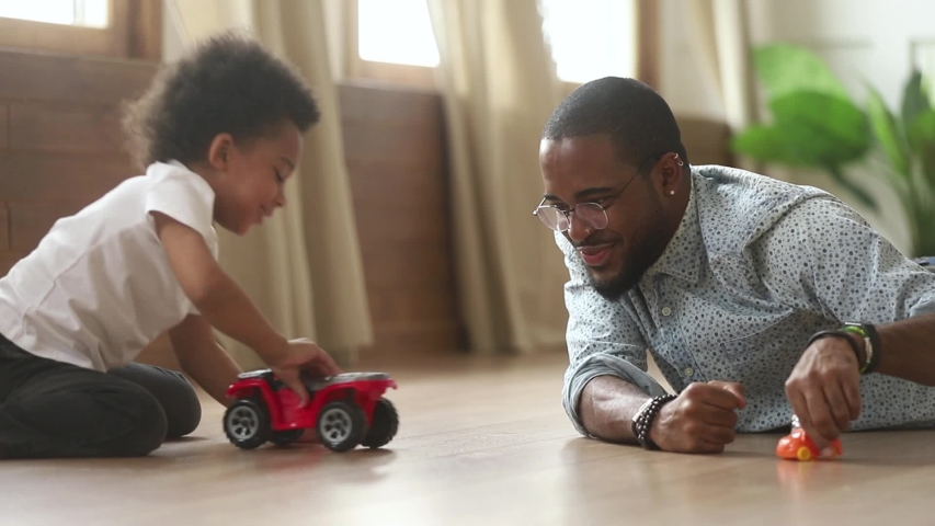 Happy african american cute little son playing toy cars with loving young dad babysitter, funny small kid son and black father having fun racing on warm floor at home, family daddy child men games