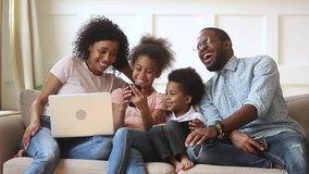 Happy african family parents and little children enjoy using devices together sit on sofa, technology addicted couple with kids having fun with laptop tablet phone at home, people gadget addiction