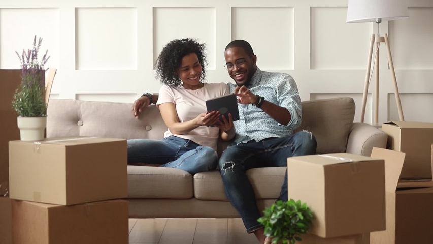 Happy african couple renters owners tenants sit on sofa use digital tablet on moving day in new house, black man and woman relax on couch with boxes discuss interior design online idea renovate home