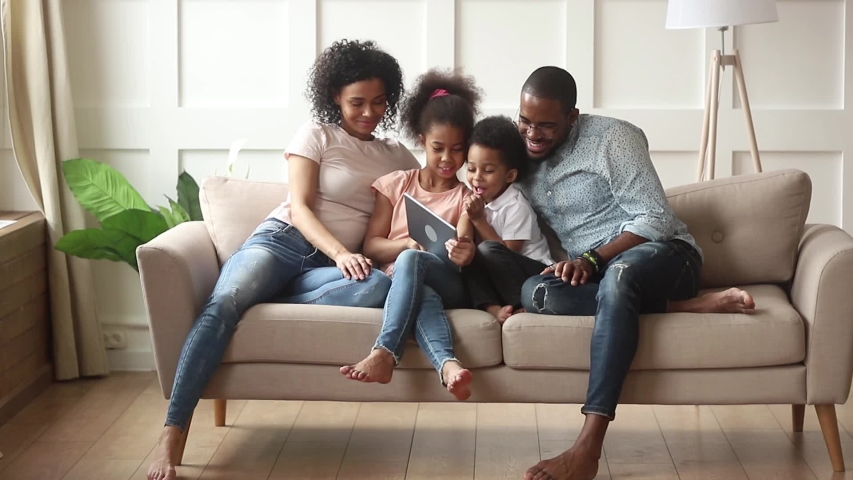 Happy african american family parents and little children using digital tablet looking at screen sit on sofa together, smiling kids holding computer laugh having fun watching cartoons online at home