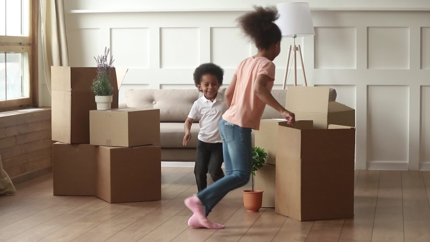 Excited funny african american kids playing active game on moving day, two happy cute little black children boy and girl running around cardboard boxes laughing in living room in new modern house #1029714026