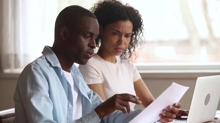 Serious african american couple talking doing paperwork using laptop together, focused family calculate pay bill rental payment online on computer holding paper at home office, mentor teaching intern Royalty-Free Stock Footage #1029714071