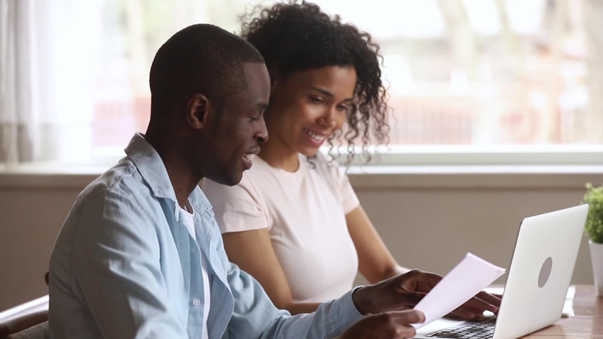 Happy african american young couple paying bank loan bills online at home, millennial black husband holding papers doing paperwork payment with wife using laptop planning budget sit at desk at home Royalty-Free Stock Footage #1029714080