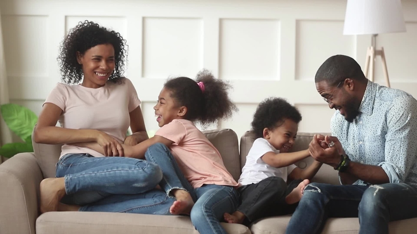 Happy african american family with kids laugh tickle sit on sofa, cheerful black parents and children having fun play at home, mom dad enjoy funny lifestyle activity with little cute son daughter | Shutterstock HD Video #1029714116