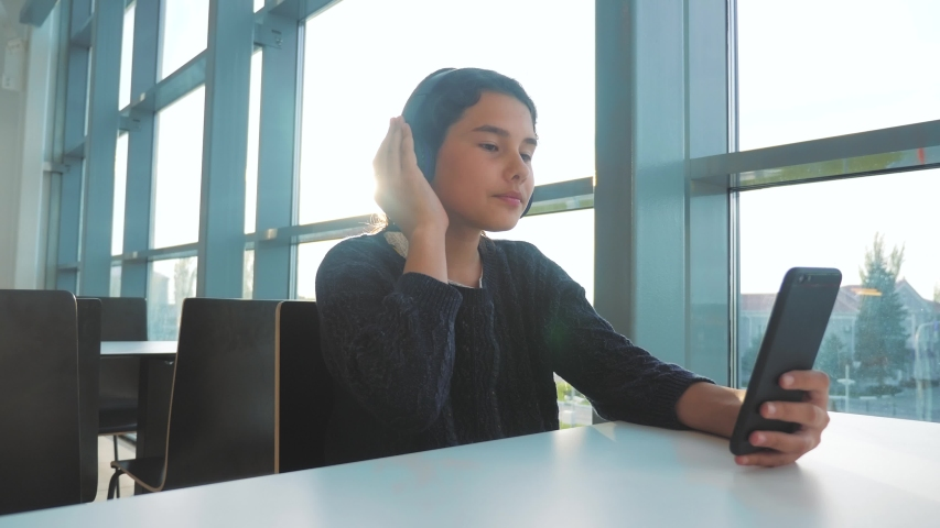 Happy young teenage girl in headphones sings and listening to the music on smartphone. teenager girl in social networks listens to music sitting lifestyle in a cafe | Shutterstock HD Video #1029717530