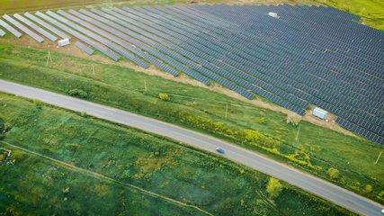 Aerial view of powerful station with solar panels generates electric current with help of sunlight is located in field near road on which pass cars. Drone shoots video of energy saving