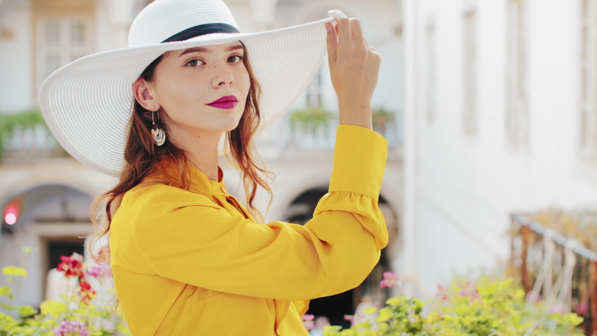 Young beautiful fashionable woman with long hair, purple lips, wearing stylish yellow blouse, white wide brim hat, hoop earrings, posing in old european city