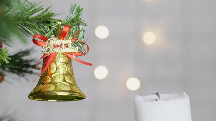 Hand with a match lights a candle next to a fir branch with a Christmas toy. | Shutterstock HD Video #1029720812