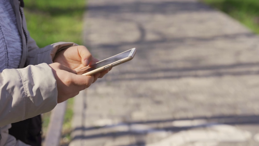 Happy woman browsing smart phone content in the street. Woman using smartphone. Touchscreen phone. Close-up. | Shutterstock HD Video #1029731297