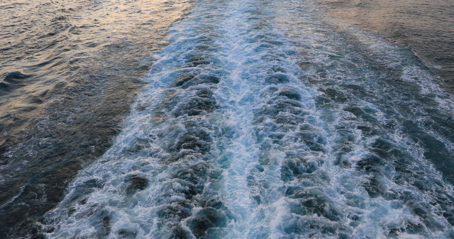 Cruise ship wake Pacific ocean beautiful sunset on water. Destination vacation travel tropical ocean sea. Beautiful blue Caribbean Ocean water wake behind large cruise ship.