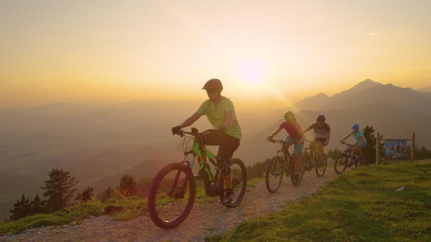 LENS FLARE, SLOW MOTION, DRONE: Cheerful active tourists riding their mountain bicycles up a scenic trail at sunset. Young travelers riding their electric bikes up a narrow mountain path at sunrise